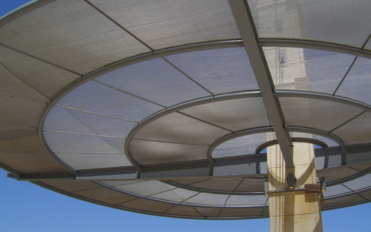 Mike Lewis Park - Grand Prairie, Texas - <br>At this open-air pavilion, cable-suspended woven wire rings of varying densities appear to hover weightlessly while providing excellent sun shading.